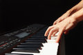Hands of musician playing the electronic piano on black background Royalty Free Stock Photo