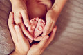 The hands of parents holding the feet of the baby. Wedding rings Royalty Free Stock Photo