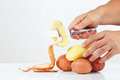 Hands peeling fresh potatoes with a knife on white background Royalty Free Stock Photos