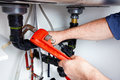 Hands of Plumber with a wrench. Royalty Free Stock Photo