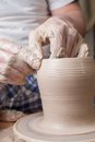 Hands of a potter creating an earthen jar on the circle Royalty Free Stock Photos