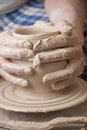 Hands of a potter creating an earthen jar on the circle Stock Image