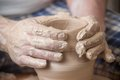 Hands of a potter creating an earthen jar on the circle Stock Images