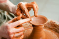 Hands of a potter creating an earthen jar on the circle in workroom Stock Image
