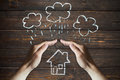 Hands protects a house from the elements - rain or storm Royalty Free Stock Photo