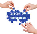 Hands with puzzle making corporate responsibility word isolated on white Stock Photos