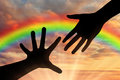 Hands reach for sky at sunset and rainbow Royalty Free Stock Photo