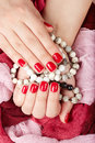 Hands with red manicured nails holding bracelets