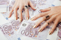 Hands of rich woman with golden manicure and many jewelry rings on cash euros close up Royalty Free Stock Image