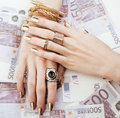 Hands of rich woman with golden manicure and many jewelry rings on cash euros close up Stock Image