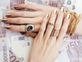 Hands of rich woman with golden manicure and many jewelry rings on cash euros close up five hundred Royalty Free Stock Images