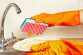 Hands in rubber gloves with dirty dishes over the sink in kitchen Royalty Free Stock Photo