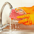 Hands in rubber gloves with sponge wash glass under running water Royalty Free Stock Photo