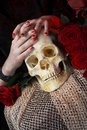 Hands and skull image of of young woman Stock Photos
