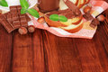 Hands spread chocolate paste on toast hazelnut with mint the table Royalty Free Stock Images