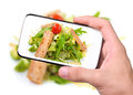 Hands taking photo grilled salmon and vegetables with smartphone Royalty Free Stock Photo