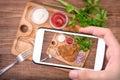 Hands taking photo pork schnitzel with smartphone.