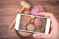 Hands taking photo raw pork schnitzel with smartphone.