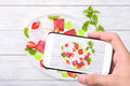 Hands taking photo strawberry yogurt ice cream popsicles with mint with smartphone. Royalty Free Stock Photo