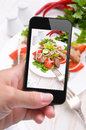 Hands taking photo vegetable salad with meat with smartphone instagram Royalty Free Stock Images
