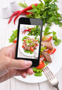 Hands taking photo vegetable salad with meat with smartphone instagram Royalty Free Stock Photo