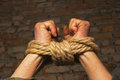 Hands tied up rope against brick wall Stock Photo