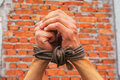 Hands tied up rope against brick wall Stock Photos