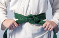 Hands tightening green belt on a teenage dressed Royalty Free Stock Photo