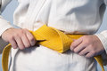 Hands tightening yellow belt on a teenage dressed in kimono Royalty Free Stock Photo