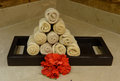 Hands towels and flowers in a spa pyramid of rolled next to red healthy Stock Photo