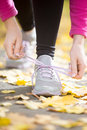 Hands tying trainers shoelaces on the fall pave Royalty Free Stock Photo