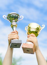 Hands of winner with gold and silver cups Royalty Free Stock Images