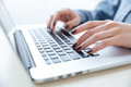 Hands of woman in blue shirt typing on laptop keyboard Royalty Free Stock Photo