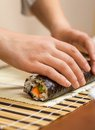 Hands of woman chef rolling up a japanese sushi with rice avocado and shrimps on nori seaweed sheet Stock Photos