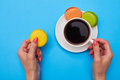 Hands of woman holding a colorful cookies and a cup of coffee over turquoise flatlay