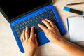 Hands of woman on the keyboard of her blue laptop Royalty Free Stock Photo