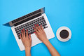 Hands of woman on a keyboard of the modern laptop over blue flat Royalty Free Stock Photo