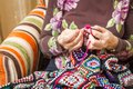 Hands of woman knitting a vintage wool quilt senior with colorful patches Royalty Free Stock Photo