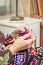 Hands of woman knitting a vintage wool quilt senior with colorful patches Stock Images