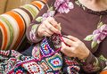 Hands of woman knitting a vintage wool quilt senior with colorful patches Stock Photo