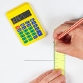 Hands at work with a pencil, digital calculator and ruler Royalty Free Stock Photo