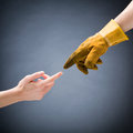 Hands of a worker and woman touching hand in dirty yellow glove bare female hand Stock Photo