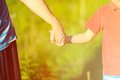 Hands of young child and old senior on nature summer background Royalty Free Stock Photography