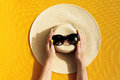 Hands of young girl holding straw hat and sunglasses on vibrant