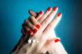 Hands of a young girl with red nails and drops of cream close-up on a blue Royalty Free Stock Photo
