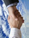 Handshake with Blue Sky and Clouds Stock Images