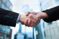 Handshake business concept on office buildings background Royalty Free Stock Photography