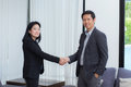 Handshake of businessman and businesswoman after successful busi