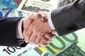 Handshake of businessmen on banknotes background Stock Photo