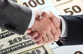 Handshake of businessmen on banknotes background Royalty Free Stock Images